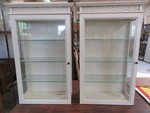 WHITE HANGING DISPLAY CABINETS WITH GLASS SHELVES AND DOORS.