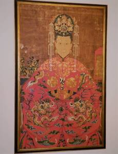 A Chinese late Qing dynasty ancestor portrait showing the wife of a senior official in brightly colored dragon decorated robe  China, late 19th Century